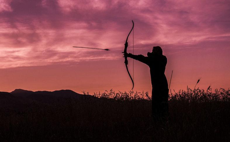 Mann schießt im Abendrot vor einem Kornfeld in gespannter Haltung einen Pfeil ab.