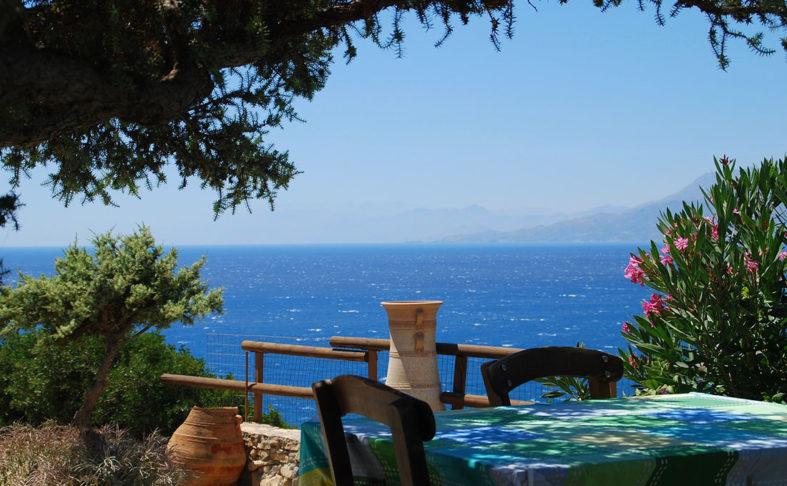 Blick von einer schattigen Terrasse auf das Meer mit Bergen im Hintergrund, Griechenland